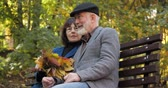 nonno : Happy elderly family spends leisure sitting on a bench in the fresh air of an autumn city park. The wife strokes her husband with a bouquet of autumn leaves. Gatherings on the street in slow motion.