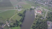old world : Aerial shot with a quadcopter of Mir Castle in Belarus slow motion. The lake is located near Mir Castle. Ancient and beautiful landmarks of Belarus, recommended for visiting. Stock Footage