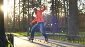 hile : A sports bearded guy on rollers makes various turns between training cones, accidentally overturning one of them. Professional training of a man in slow motion on roller skates in the autumn.