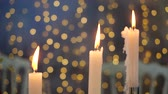 enterro : Bright beautiful background in the form of lights for three candles. Cozy atmosphere and preparation for the winter holidays. Close-up view of burning candles on a background of blurry lights.