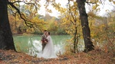 evlenmek : Young attractive loving couple of newlyweds in autumn forest by the lake. Couple in love newlyweds among Beautiful colorful seasonal foliage. wedding in the woods in nature Stok Video