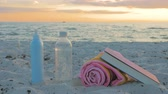 Beach accessories, a bottle of water, towel, sunglasses, sunscreen and a book lying on a beach at sunset. Holidays background and people concept Vídeos