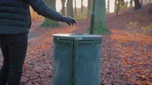 しわくちゃな : man throws trash in a trash bin in a park on a sunny autumn day