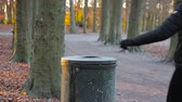 優しい : man throws trash in a trash bin in a park on a sunny autumn day