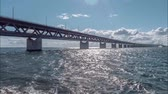 kopenhag : Timelapse Oresundsbron with blue sky and white clouds. The bridge between Sweden and Denmark. Stok Video