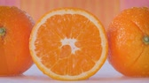 мандарин : Sliding along whole and sliced oranges where water is spraying over them
