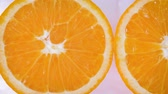 мандарин : Sliding along oranges slices on a white and wet background. Close up Стоковые видеозаписи