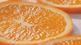 Sliding along oranges slices on a white and wet background. Close up Vídeos