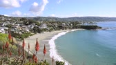 overlooking : A beautiful cliff side view of Crescent Bay Beach in Laguna Beach, California shows the scenic, turquoise water and the white sand beach.