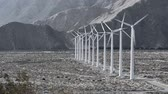 ambiental : A row of windmills turning with the wind generate power for a local community.