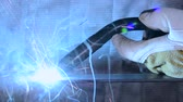 kaynakçı : A metal worker welds a piece of steel, generating blue flames and sparks Stok Video