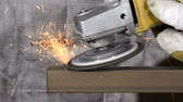 warsztat : A metal worker uses a grinding wheel to shave off some steel from square stock Wideo