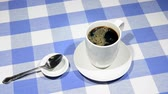 csészealj : Cup on blue checkered tablecloth being filled with hot coffee