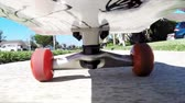 patim : A camera is mounted under a skateboard while a rider moves along a sidewalk. Stock Footage
