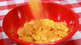 processado : Corn flake cereal being poured into a red bowl for breakfast