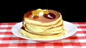 приправа : Sweet maple syrup being poured over a hot, freshly buttered stack of pancakes. Стоковые видеозаписи