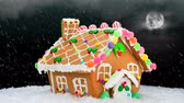 fantezi : A gingerbread house during a cold, snowy Christmas evening shows a festive setting with a cloudy, black sky, bright moon and delicious cookie decoration. Stok Video
