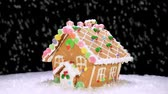 świety mikołaj : A rotating gingerbread house with candy and decorations during a snowy Christmas holiday Wideo
