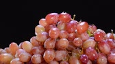 empilhados : While in the produce section, a grocer sprays cool water over delicious grapes to keep them fresh