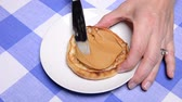 приправа : A woman at a diner spreads peanut butter on her freshly toasted English muffin before eating it