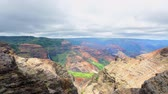 гавайский : Time lapse of a Waimea Canyon overlook during a partly cloudy day shows the colorful, textured patterns of the rocky terrain and cloud movements casting shadows on the colorful terrain.