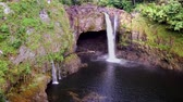 гавайский : Beautiful Rainbow Falls in Hilo Hawaii forms cascading flows into a natural pool and often casts colorful rainbows when the sun position is just right, as shown here.