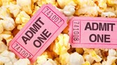 volný čas : Motion over the top of a tub of fresh, hot popcorn with pink movie tickets for admission into the theater. Dostupné videozáznamy