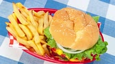 batatas fritas : A delicious, fully loaded hamburger in a traditional red serving basket served with French fries Stock Footage