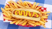 batatas fritas : A freshly barbecued hotdog with traditional yellow mustard surrounded with French fries served in a classic red basket.