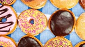 pronto para comer : Delicious bakery donut assortment including chocolate, glazed and cake on top of a traditional blue and white checkered tablecloth. Stock Footage