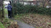 živý plot : Middle aged man putting up the hood on his cagoule on a wet, overcast autumn day, walking up a garden path away from the house and out of the garden gate. The garden is a little unkempt and covered with fallen leaves.