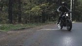 cafe racer : A guy in a black leather jacket and helmet riding a classic motorcycle on a forest road. View from the back, focus on road, motorcyclist defocused