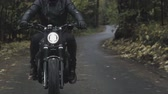 acımasız : A guy in a black leather jacket and helmet riding a classic motorcycle on a forest road. Stok Video