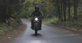cafe racer : A guy in a black leather jacket and helmet riding a classic motorcycle on a forest road. Stock Footage