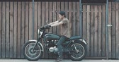 cafe racer : Handsome rider guy with beard and mustache parked classic style motorcycle near wooden wall of garage. Urban lifestyle 4k video