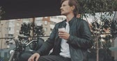 cafe racer : Young caucasian man biker drinking coffee while standing near the classic vintage motorcycle from 1970s on the street and looking away. Urban lifestyle scene. 4K video shooting by handheld gimbal Stock Footage