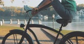 cyklista : Beautiful summertime mood shot of young woman or girl riding bicycle through promenade, in stylish outift, pedalling next to trees in sun light, 4K video shooting by handheld gimbal