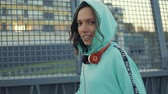 come : Young woman throw popcorn to camera. Girl in mint color sweatshirt hoodie having fun. Outdoors urban city lifestyle portrait. slow motion video shooting by handheld gimbal