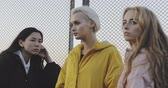 gossip : Portrait of three young multiracial women talking in street. Female models wearing jeans and long jacket coat. 4k video steadicam shot . Evening urban city outdoor style