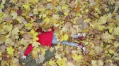 setembro : Cute girls playing with yellow leaves on beautiful autumn day. Happy children having fun in city park. Little female model dressed in red coat and hat lying over leaves and smiling. Slow motion video