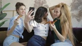 food photo : Happy multiethnic friends eating pizza at casual house party. Young women spend fun time together. Three female models making selfies , grimasing and posing funny. Indoor slow motion footage