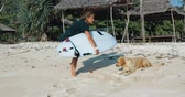 shortboard : young surfer woman with surfboard and dog