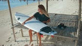 shortboard : Girl surfer waxing her surfboard