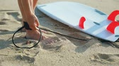 shortboard : Young surfer woman beginner fastens leash across leg