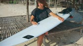 waxing : Girl surfer waxing her surfboard