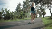 shortboard : girl go to beach with skateboard Stock Footage