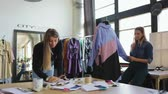 femmes : Young female tailor workers, modeller and stylist discussing clothing design in workshop
