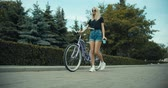 bisikletçi : Young woman walking on city streets with bicycle and drinking coffee to go, sunshine, 4K slow motion video footage Stok Video