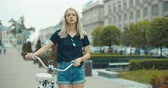 bisiklete binme : Young modern woman riding bicycle in city. 4K slow motion video footage 60 fps