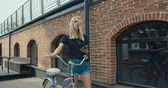 bisiklete binme : Young modern woman riding bicycle in city. Girl texting reading messages on smartphone. 4K slow motion video footage 60 fps